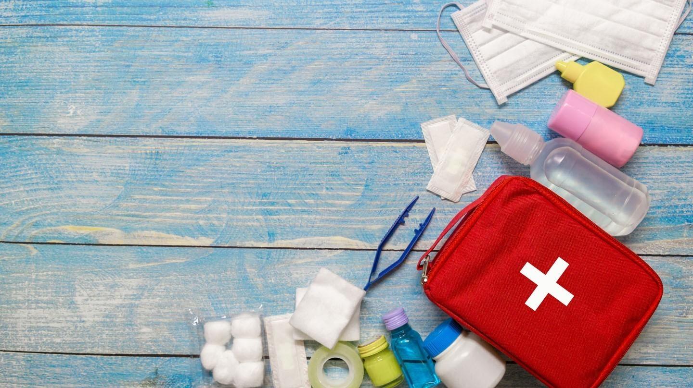 Urlaub 2020: Eine rotes Verbandtäschchen mit weißem Kreuz. Drumherum liegen Mund-Nasen-Masken und Verbandutensilien.